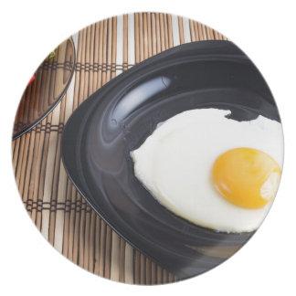 Close-up top view on a black plate with fried egg