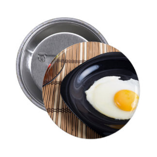 Close-up top view on a black plate with fried egg 2 inch round button