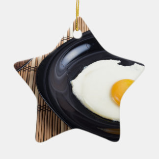 Close-up top view on a black plate with fried egg ceramic star ornament