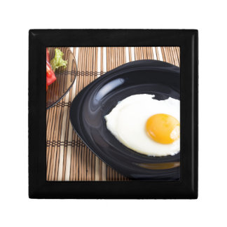 Close-up top view on a black plate with fried egg gift box