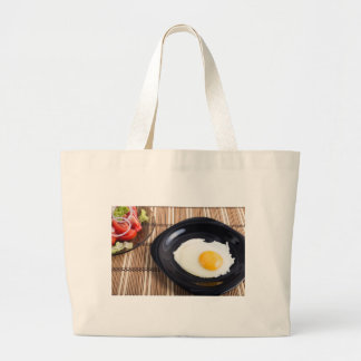 Close-up top view on a black plate with fried egg large tote bag