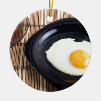 Close-up top view on a black plate with fried egg round ceramic ornament