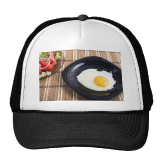 Close-up top view on a black plate with fried egg trucker hat