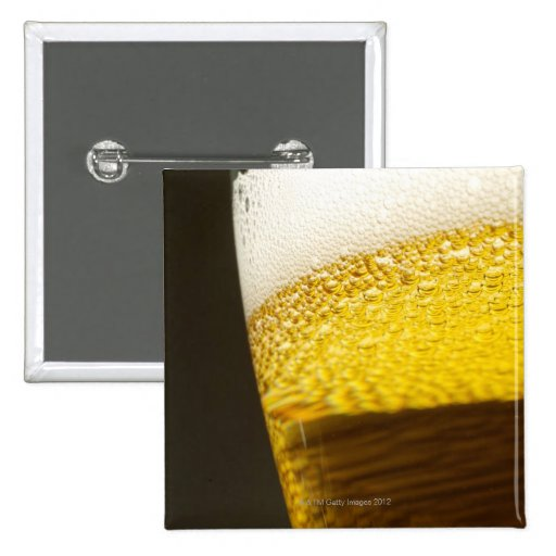 Close up view of beer, bubbles and foam in a pinback button