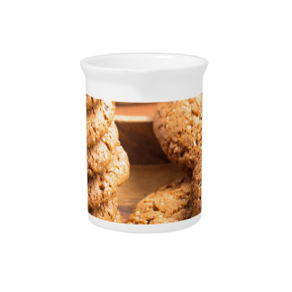 Close-up view on oat biscuits in wooden boxes beverage pitcher