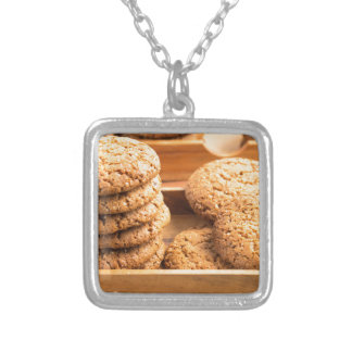 Close-up view on oat biscuits in wooden boxes silver plated necklace