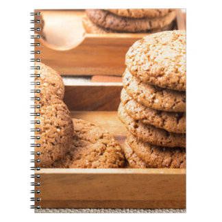 Close-up view on oat biscuits in wooden boxes spiral notebook