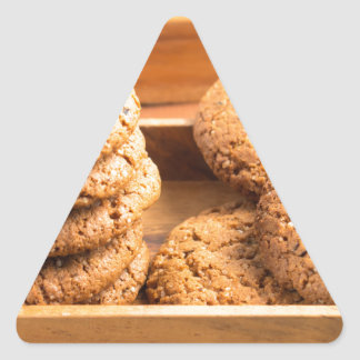 Close-up view on oat biscuits in wooden boxes triangle sticker