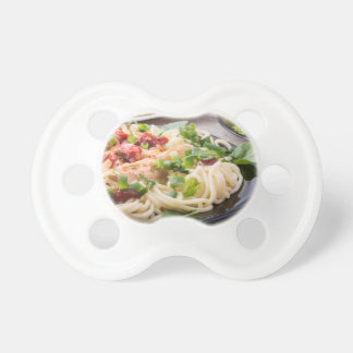 Closeup black plate with spaghetti pacifiers