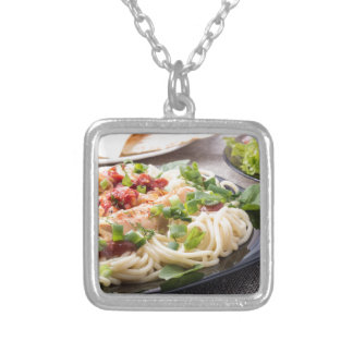 Closeup black plate with spaghetti silver plated necklace