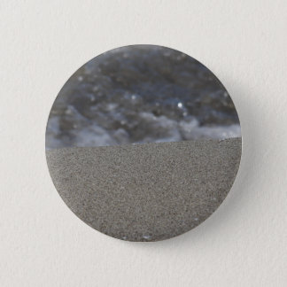 Closeup of sand beach with sea blurred background 2 inch round button