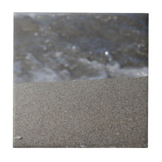 Closeup of sand beach with sea blurred background ceramic tile