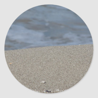 Closeup of sand beach with sea blurred background classic round sticker