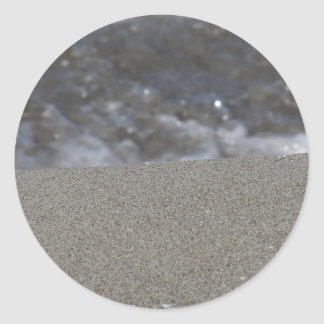 Closeup of sand beach with sea blurred background classic round sticker