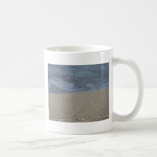 Closeup of sand beach with sea blurred background coffee mug