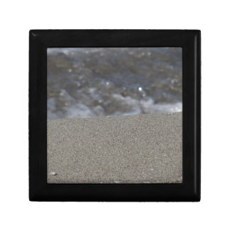 Closeup of sand beach with sea blurred background gift box
