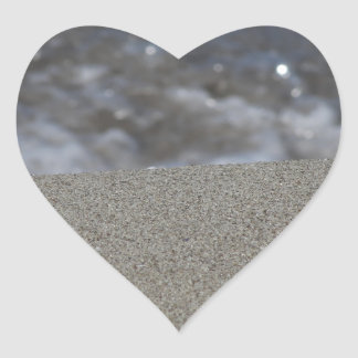 Closeup of sand beach with sea blurred background heart sticker