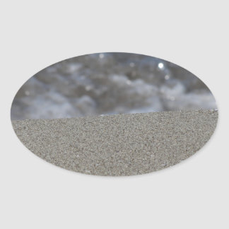Closeup of sand beach with sea blurred background oval sticker