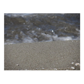 Closeup of sand beach with sea blurred background postcard