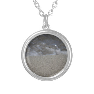Closeup of sand beach with sea blurred background silver plated necklace