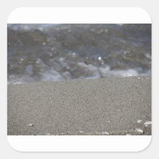 Closeup of sand beach with sea blurred background square sticker