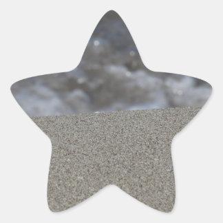 Closeup of sand beach with sea blurred background star sticker