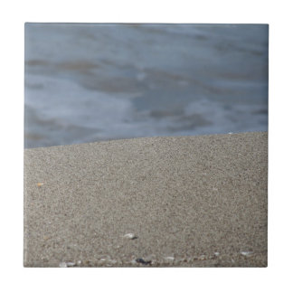 Closeup of sand beach with sea blurred background tiles