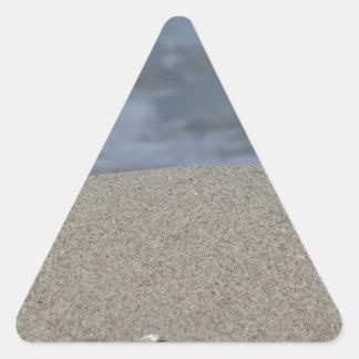 Closeup of sand beach with sea blurred background triangle sticker