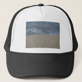 Closeup of sand beach with sea blurred background trucker hat
