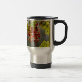Closeup red grapes among leaves travel mug