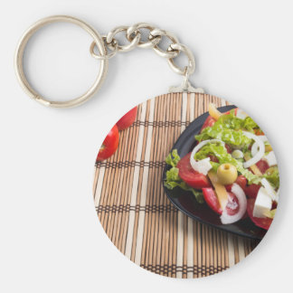 Closeup view fresh natural salad with raw tomato basic round button keychain