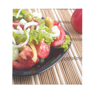 Closeup view fresh natural salad with raw tomato notepad