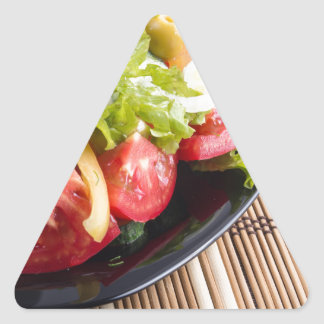 Closeup view fresh natural salad with raw tomato triangle sticker