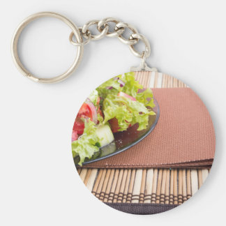 Closeup view of a plate with fresh salad of raw basic round button keychain