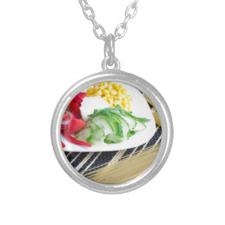 Closeup view of a vegetarian dish of raw vegetable silver plated necklace