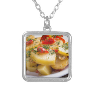 Closeup view of a vegetarian dish of stewed potato silver plated necklace
