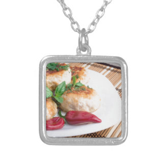 Closeup view of the fried meatballs on a stripe silver plated necklace