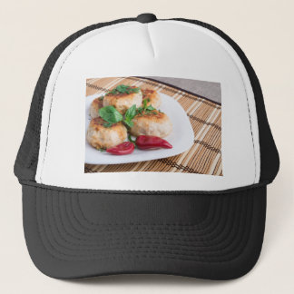 Closeup view of the fried meatballs on a stripe trucker hat
