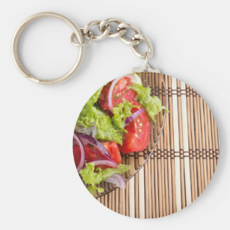 Closeup view on a fragment of a plate with salad basic round button keychain