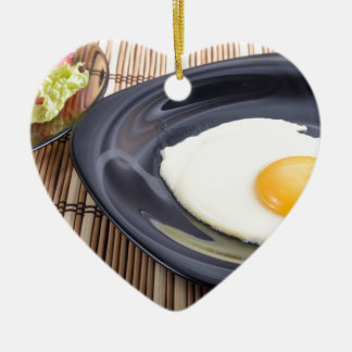 Closeup view on fried eggs with yolk on a plate ceramic heart ornament