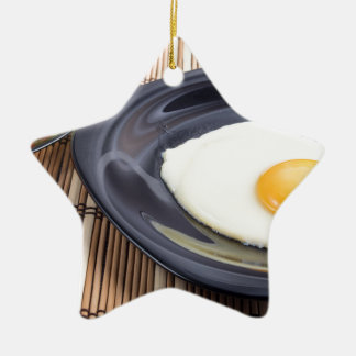 Closeup view on fried eggs with yolk on a plate ceramic star ornament