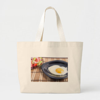 Closeup view on fried eggs with yolk on a plate large tote bag