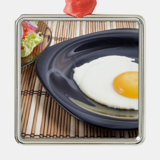 Closeup view on fried eggs with yolk on a plate Silver-Colored square ornament
