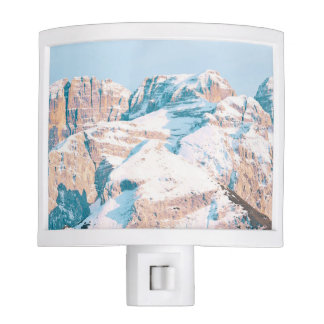 Closeup view or snow-dusted mountains night lights