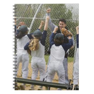 Coach with baseball team notebook