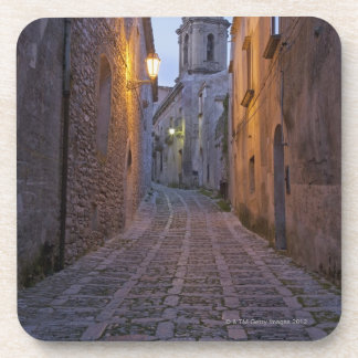 Cobbled alleyway of old city lit up at night drink coaster