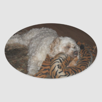 Cockapoo dog rleaxing on his tiger striped bed oval sticker