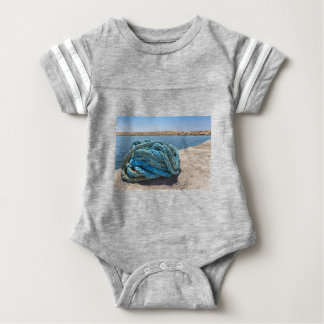 Coiled blue mooring rope at water in greek cave baby bodysuit
