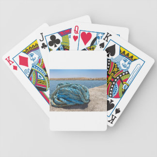 Coiled blue mooring rope at water in greek cave bicycle playing cards