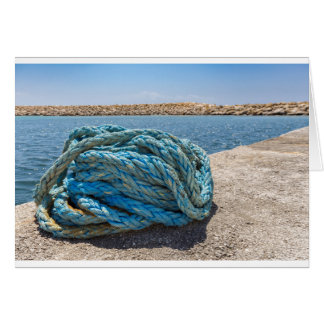 Coiled blue mooring rope at water in greek cave card